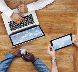 FIVE10 Web Development - Aerial shot of multiple people using mobile devices around a wood table